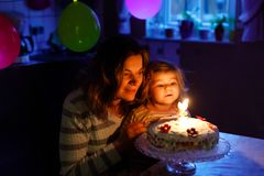 Adorable little toddler girl celebrating second birthday. Baby child daughter and young mother blowing candles on cake. And candles. Happy healthy family royalty free stock images