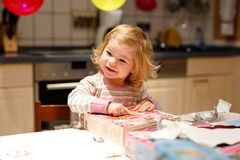 Adorable little toddler girl celebrating second birthday. Baby child unpacking gifts. Happy healthy child is suprised. About big boxes and toys present stock photography
