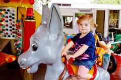 Adorable little toddler girl riding on animal on roundabout carousel in amusement park. Happy healthy baby child having royalty free stock photo