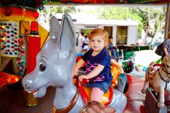 Adorable little toddler girl riding on animal on roundabout carousel in amusement park. Happy healthy baby child having royalty free stock images