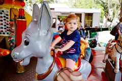 Adorable little toddler girl riding on animal on roundabout carousel in amusement park. Happy healthy baby child having stock images