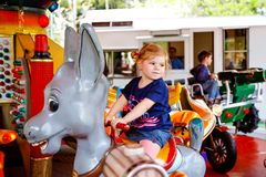 Adorable little toddler girl riding on animal on roundabout carousel in amusement park. Happy healthy baby child having royalty free stock photography
