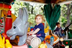 Adorable little toddler girl riding on animal on roundabout carousel in amusement park. Happy healthy baby child having stock photo