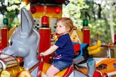 Adorable little toddler girl riding on animal on roundabout carousel in amusement park. Happy healthy baby child having stock photos
