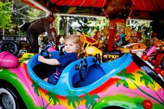 Adorable little toddler girl riding on funny car on roundabout carousel in amusement park. Happy healthy baby child stock photos