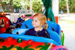 Adorable little toddler girl riding on funny car on roundabout carousel in amusement park. Happy healthy baby child royalty free stock photography