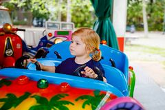 Adorable little toddler girl riding on funny car on roundabout carousel in amusement park. Happy healthy baby child royalty free stock photo