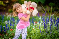 Adorable toddler girl holding white teddy bear. Adorable little toddler girl with a white teddy bear having fun in summer park on beautiful sunny day with yellow stock photos