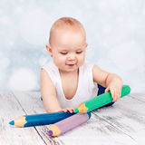 Adorable little toddler playing with big crayons Royalty Free Stock Photo
