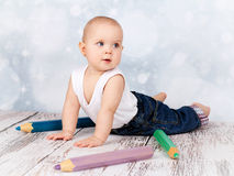 Adorable little toddler playing with big crayons Royalty Free Stock Image