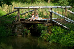 Adorable Little Twin Brothers Sitting on the Edge of Wooden Bridge and Fishing on Beautiful Lake Stock Photo