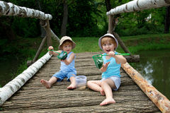 Adorable Little Twin Brothers Sitting on a Wooden Bridge and Holding a Fishnet Full of Fish at the Lake Stock Images