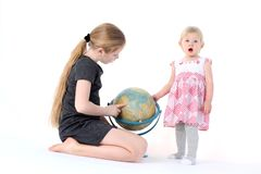 Adorable little two sisters with globe Royalty Free Stock Photo