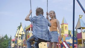 Cute girl with long hair swinging on a swing cute boy outdoors. Couple of happy children. Funny carefree kids in love. stock video footage