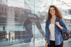 Adorable lovely glad young female with curly hair, wears fashionable denim jacket and carries rucksack, comes in shopping centre f stock photography