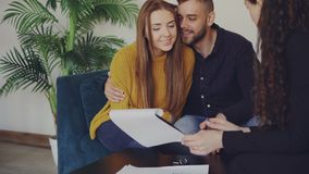 Adorable couple is checking papers during meeting with realtor in nice new apartment. Young people are sitting on sofa. Adorable loving couple is checking papers stock footage