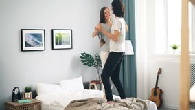 Adorable loving couple dancing on bed at home hugging having fun. Adorable loving couple dancing on bed at home and hugging having fun in modern light house stock footage