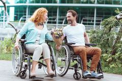 Adorable mature couple laughing during romantic date. Never bored together. Positive minded disabled people beaming while sitting in their wheelchairs and royalty free stock images