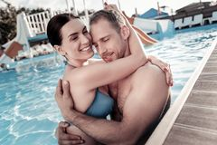 Adorable millennial couple hugging and smiling in swimming pool stock photos