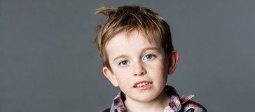 Adorable mischievous young kid with freckles and messy red hair Stock Images