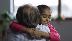 Loving little girl embracing her grandfather stock video footage