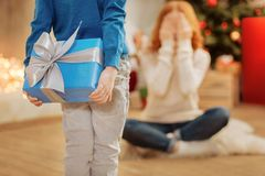 Thoughtful boy giving his mother christmas present. Adorable moment. Close up on a kid wearing casual attire holding a beautifully wrapped gift behind his back royalty free stock images