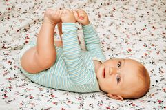 Portrait of cute baby boy. Adorable 5-6 months baby boy lying on the bad and playing with his feet Royalty Free Stock Photo