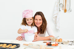 Adorable mother and daughter preparing a daugh. Portrait of an adorable mother and daughter preparing a daugh together in the kitchen stock photo