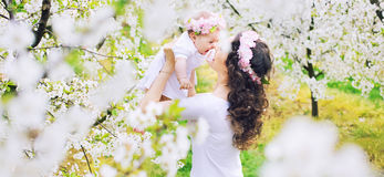 Adorable mother and her little child resting in a spring orchard Stock Photography