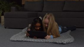 Cute little girls playing on tablet pc at home. Adorable multi ethnic preteen girls browsing social networks on digital tablet while lying on the floor in stock video footage