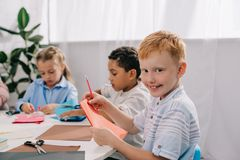 Adorable multicultural kids making paper applique. In classroom stock photos