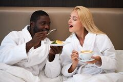 Adorable multiethnic couple have breakfast in hotel