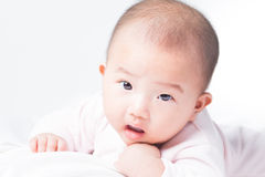 Adorable newborn Asian baby. Adorable Asian baby 4-5 months old on white bed & background. Portrait studio light isolated Royalty Free Stock Image