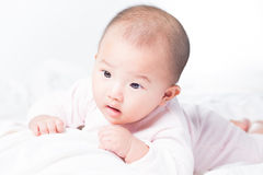 Adorable newborn Asian baby. Adorable Asian baby 4-5 months old on white bed & background. Portrait studio light isolated Stock Photo