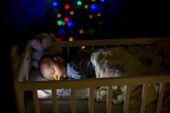 Adorable newborn baby boy, sleeping in crib at night. Little boy in blue striped pajamas taking a nap in dark room, christmas decoration in the room, winter royalty free stock photography