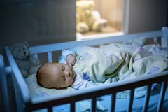 Adorable newborn baby boy, sleeping in crib at night. Little boy in white pajamas taking a nap in dark room. Bedroom interiоr with lamp and teddy bear in royalty free stock photography