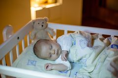 Adorable newborn baby boy, sleeping in crib at night Stock Image