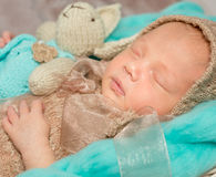 Adorable newborn baby with bunny-toy in cot Stock Images