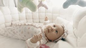 Adorable newborn baby girl in her cot Stock Photos