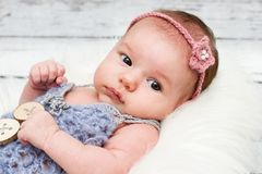Adorable newborn baby girl looking towards camera. Beautiful and adorable little baby girl lying on the fur and looking towards camera, studio portrait Royalty Free Stock Photos