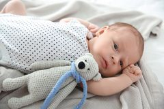 Adorable newborn baby with toy bear lying on blanket stock photos