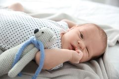 Adorable newborn baby with toy bear lying royalty free stock images