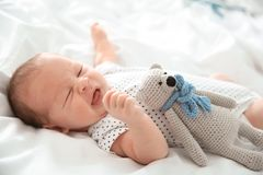 Adorable newborn baby with toy lying stock photography