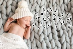Adorable newborn baby in warm hat lying on bed royalty free stock image