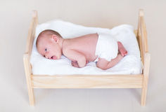 Adorable newborn baby in a wooden toy bed Royalty Free Stock Image