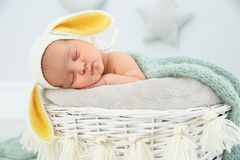 Adorable newborn child wearing bunny ears hat in baby nest royalty free stock images
