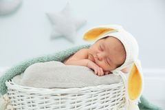 Adorable newborn child wearing bunny ears hat in baby nest royalty free stock photography