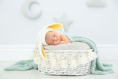 Adorable newborn child wearing bunny ears hat in baby nest stock photo