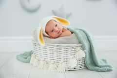 Adorable newborn child wearing bunny ears hat in baby nest stock image