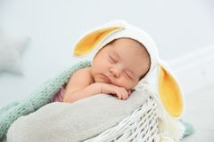 Adorable newborn child wearing bunny ears hat in baby nest stock photography